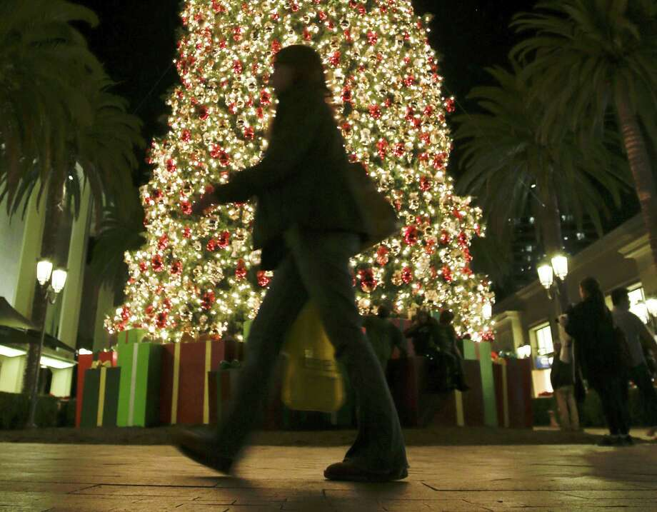 In this Thursday, Dec. 20, 2012, photo, a holiday shopper walks past a large Christmas tree at Fashion Island shopping center in Newport Beach, Calif. A last-minute surge in spending helped many major U.S. retailers report better-than-expected sales in December, a relief for stores that make up to 40 percent of annual revenue during the holiday period.  (AP Photo/Chris Carlson) Photo: Chris Carlson