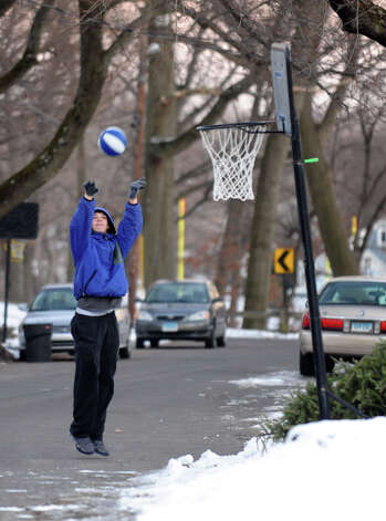 Gareth Kubic, of Milford, plays some basketball by himself in front of his home along Landon Street in Stratford Conn. on Thursday January 3, 2012. Photo: Christian Abraham
