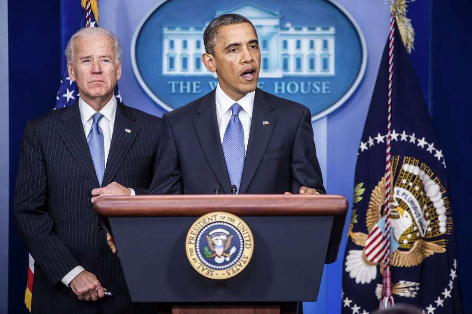 U.S. President Barack Obama speaks as U.S. Vice President Joe Biden looks on during the push to avoid the fiscal cliff, but he did nothing to address the nation's staggering debt problem. Photo: Brendan Hoffman, Bloomberg / © 2013 Bloomberg Finance LP