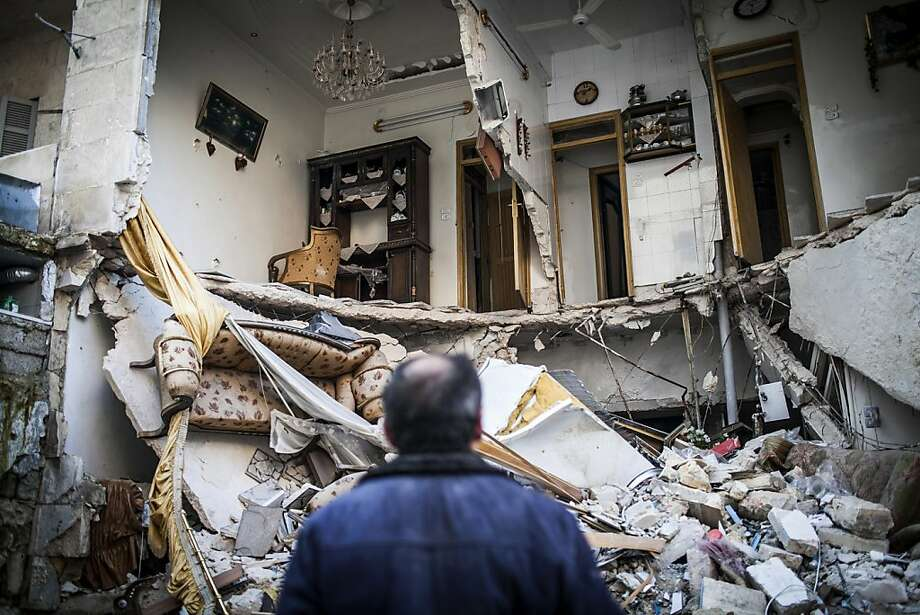 A man looks at a ruined home in Aleppo, Syria. Meanwhile, a car bomb at a gas station killed at least nine people in Damascus, while deadly air strikes wrecked apartment towers in Douma. Photo: Andoni Lubaki, Associated Press