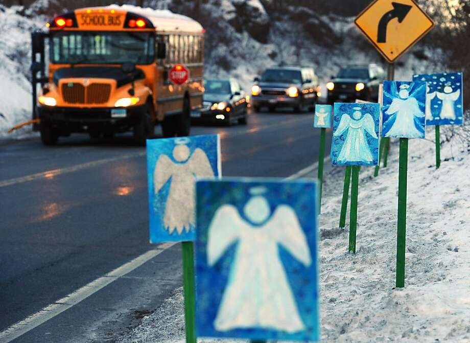 Angels on the shoulder: A school bus traveling from Newtown to Monroe, Conn.,  stops across from 26 roadside angel signs on the first day of classes for Sandy Hook Elementary School students since the Dec. 14 shooting. Photo: Jessica Hill, Associated Press