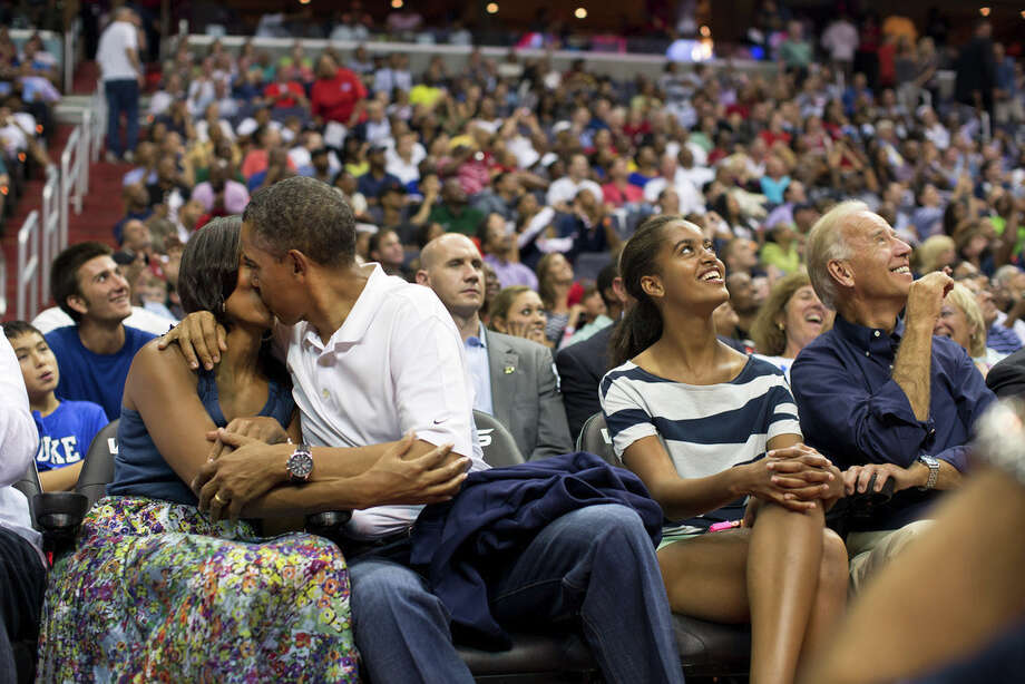July 16, 2012The President and First Lady were attending the game between the U.S. Men's Olympic basketball team and Brazil in Washington, D.C. During the first half, the jumbotron flashed couples on their 'Kiss Cam', where they are then induced by the crowd to kiss each other. But neither the President or First Lady saw themselves when they were flashed on the 'Kiss Cam', and some in the audience booed when they didn't kiss. At halftime, as we walked to the locker room to visit the U.S. team, daughters Malia and Sasha were asking their parents why they hadn't kissed during their 'Kiss Cam' moment. Both the President and First Lady said they hadn't even realized what had happened and didn't know why people were booing. So in the second half, when they appeared again on the 'Kiss Cam', the President leaned over to kiss the First Lady amidst audience cheers as Malia and the Vice President watched overhead on the jumbotron. (Official White House Photo by Pete Souza)