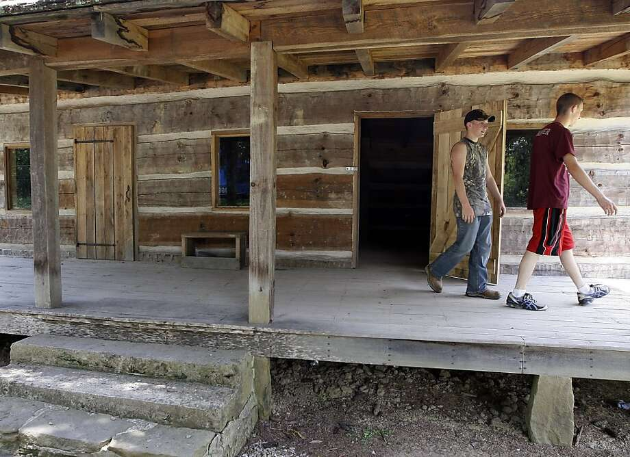 Jordan Stamper (right) and James Ball look over a cabin that marks the site of key events in the feud. Photo: James Crisp, Associated Press