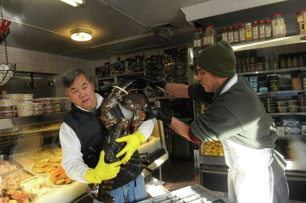 John Tung owner of Lobster Bin, left, holds a 25-pound lobster at the store on Field Point Road in Greenwich, Conn., Thursday, Jan. 3, 2013. Tung plans to release the lobster back into the wild in the near future. Photo: Helen Neafsey / Greenwich Time