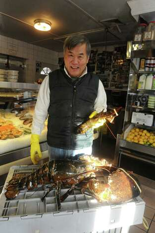 John Tung, owner of Lobster Bin, left, holds a 25-pound lobster at the store on Field Point Road in Greenwich, Conn., Thursday, Jan. 3, 2013. Tung plans to release the lobster back into the wild in the near future. Photo: Helen Neafsey / Greenwich Time