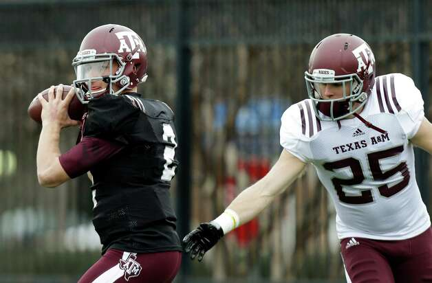 Texas A&M quarterback Johnny Manziel (2) looks to pass as defensive back Clay Honeycutt (25) reaches in during practice for the Cotton Bowl NCAA college football game, Sunday, Dec. 30, 2012, in Dallas. Texas A&M is scheduled to play Oklahoma on Jan. 4, 2013. (AP Photo/LM Otero) Photo: LM Otero, Associated Press / AP
