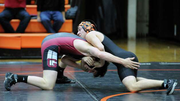 At right, Christian Llanos of Stamford against Dan Gutman, right, of Greenwich, in the 145 pound match that Llanos won during the boys high school wrestling match between Stamford and Greenwich at Stamford High School, Thursday night, Jan. 3, 2013. Photo: Bob Luckey / Greenwich Time