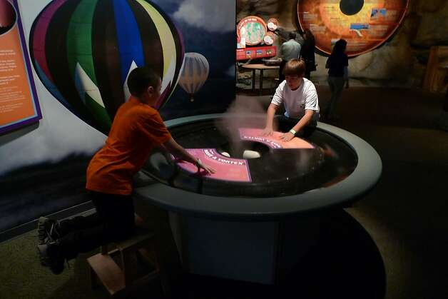 Young visitors experiment with a weather-related display at the Arizona Science Center, a family-friendly museum. Photo: Spud Hilton, The Chronicle