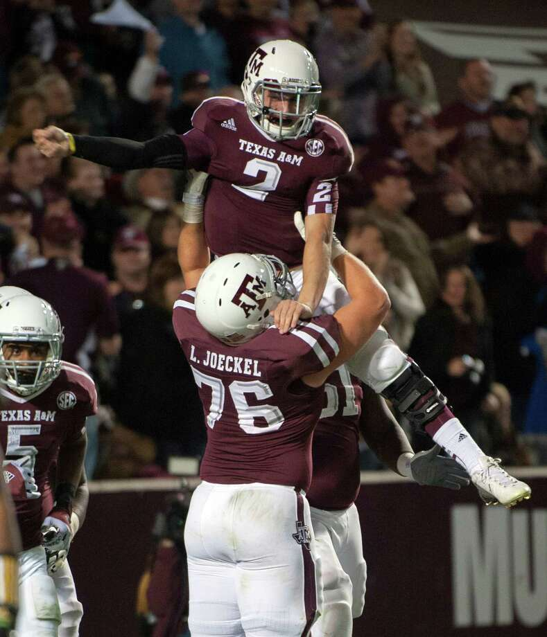 Texas A&M quarterback Johnny Manziel (2) gets a lift from Luke Joeckel (76) after running 18-yards for a touchdown during the third quarter of an NCAA college football game against Missouri, Saturday, Nov. 24, 2012, in College Station, Texas. (AP Photo/Dave Einsel) Photo: Dave Einsel, Express-News / FR43584 AP