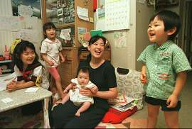 ADVANCE FOR SUNDAY, AUG. 2--Kazuhiro Sasaya, 3, balances a plastic bead on his nose as he is watched by his mother Michiko, holding two-month old daughter Miyo, and his sisters Naoko, 6, left, and Yukiko, 4, in their Tokyo apartment July 1,1998. The family is one of Japan's dwindling number of big families, which in a country with a plummeting birth rate, means any one with more than two kids. (AP Photo/Shizuo Kambayashi)