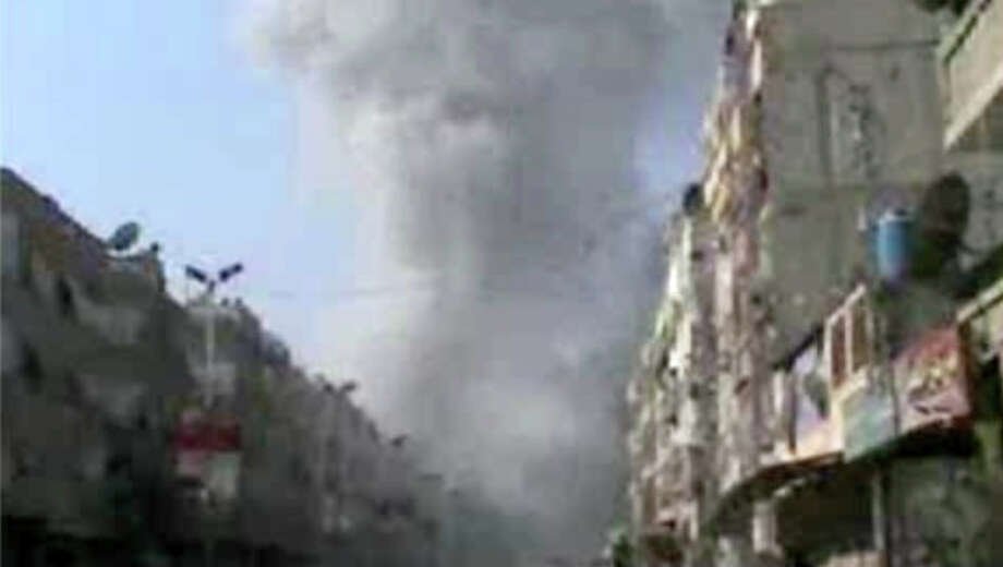 In this image taken from video obtained from Bambuser, which has been authenticated based on its contents and other AP reporting, smoke rises from buildings after an airstrike hit Douma City, Syria on Thursday, Jan. 3, 2013. Airstrikes continued across Syria on Thursday as Syrian President Bashar Assad's military stepped up its assault on areas that surround the nation's capital. (AP Photo/Bambuser via AP video) Photo: Anonymous