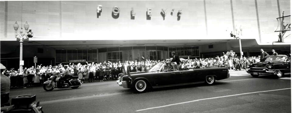 President John F. Kennedy greets Houstonians as his motorcade drives past Foley's in Houston.