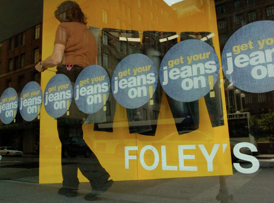 An unidentified woman works in a display window at Foley's store downtown on Main St. Thursday,  July 28, 2005. Federated Department Stores announced plans to convert Foley's  to Macy's. Photo: MELISSA PHILLIP, HOUSTON CHRONICLE / HOUSTON CHRONICLE