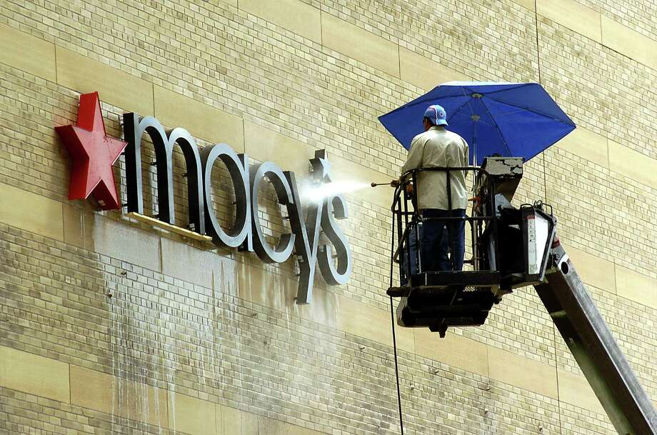 Nicholas Rodriguez and Jaime Perez from State Sign power wash off any marks left by the old Foley's sign after replacing it with a Macy's sign on Dallas Street downtown Wednesday Aug. 9, 2006. Photo: Dave Rossman, For The Chronicle / Freelance