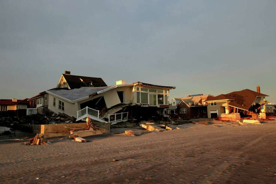 Homes destroyed by Superstrom Sandy front the beach in the Rockaways section of New York, Wednesday, Jan. 2, 2013.  House Speaker John Boehner's decision to cancel an expected vote Tuesday night on aid for Superstorm Sandy victims outraged lawmakers from New York, New Jersey and elsewhere, including many in his own party.   (AP Photo/Seth Wenig) Photo: Seth Wenig