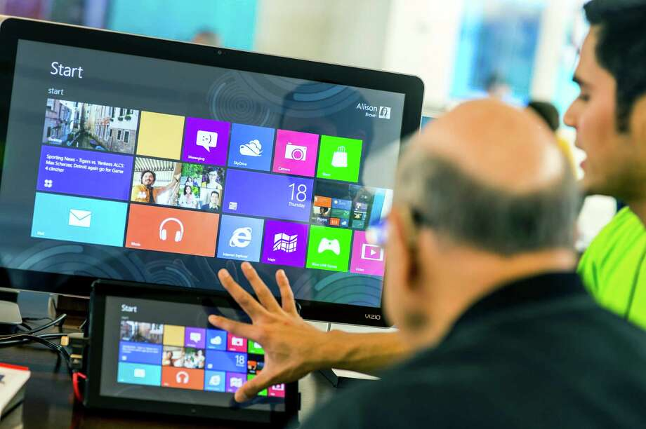 An employee at a Microsoft store, right, explains the new Windows 8 operating system on a tablet in Bellevue, Wash., Oct. 18, 2012. Windows 8's new design, which features many bold changes, is likely to cause some head-scratching when it goes on sale this Friday. (Stuart Isett/The New York Times) Photo: STUART ISETT / NYTNS