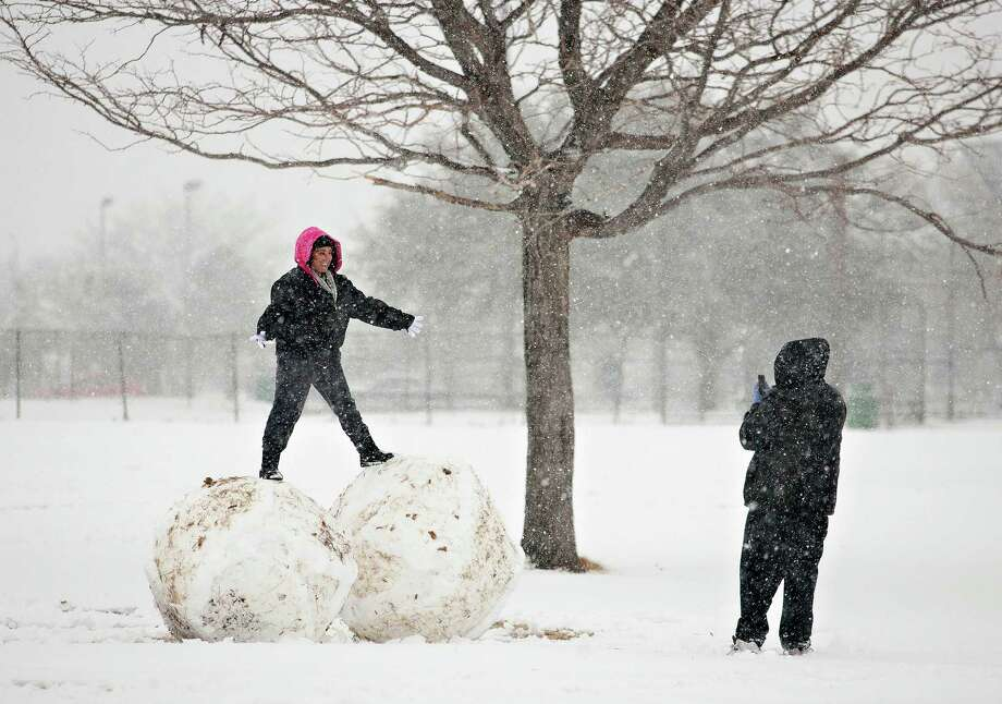 Victoria Luna poses for George Olivas on top of 2 giant snowballs at Album Eastwood Park as snow blankets the area Thursday, Jan. 3, 2013 in El Paso, Texas.  Up to eight inches of snow, with isolated amounts approaching 10 inches, were expected across West Texas as the storm moved across the region. Photo: Fernie Castillo, The El Paso Times / The El Paso Times