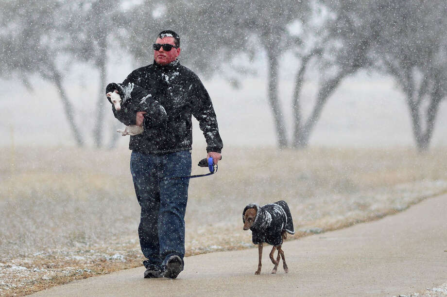 Ryan Liddle of Houston, visiting his parents in Odessa, Texas walks his dog Max, while he carries his other dog Lady in the snow Thursday afternoon, Jan. 3, 2013 along the hiking trail at the University of Texas - Permian Basin. Photo: Mark Sterkel|, Associated Press / Odessa American