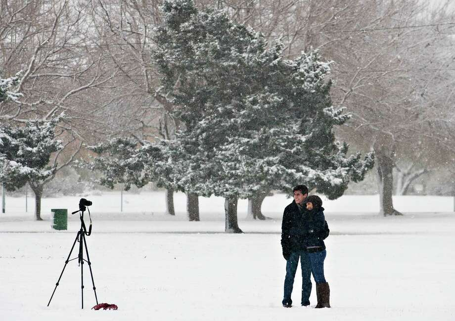A couple take some self portraits at Album Eastwood Park as snow blankets the area Thursday, Jan. 3, 2013 in El Paso, Texas.  Up to eight inches of snow, with isolated amounts approaching 10 inches, were expected across West Texas as the storm moved across the region. Photo: Fernie Castillo, The El Paso Times / The El Paso Times