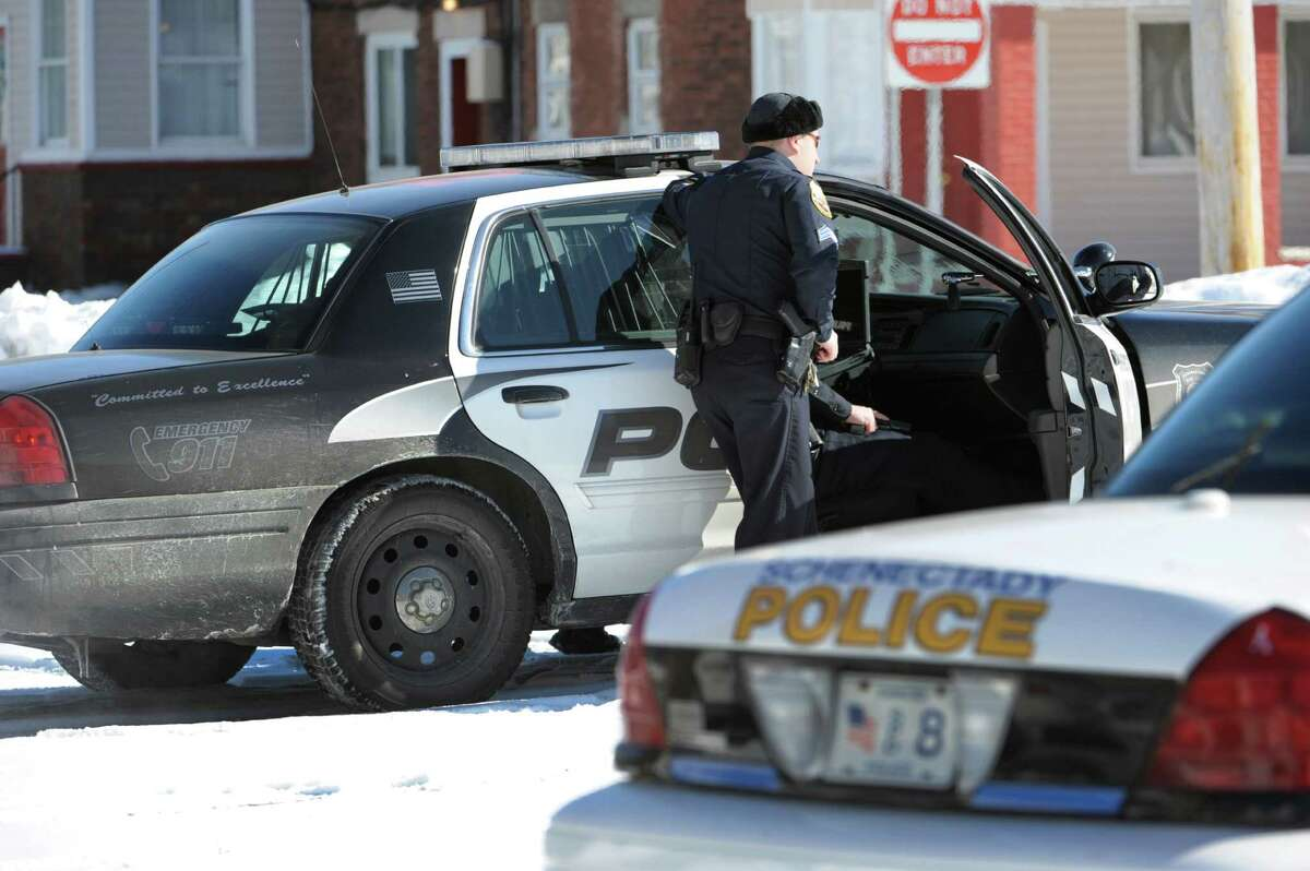Schenectady police officers watch as a man is taken in to custody on Feb. 22, 2011, on State Street in Schenectady, N.Y. The Civil Rights Division of the U.S. Justice Department has closed a decade-long probe of the city police force after concluding that the department has adequately addressed concerns related to the use of excessive force, illegal searches and seizures and other issues. (Skip Dickstein / Times Union archive)