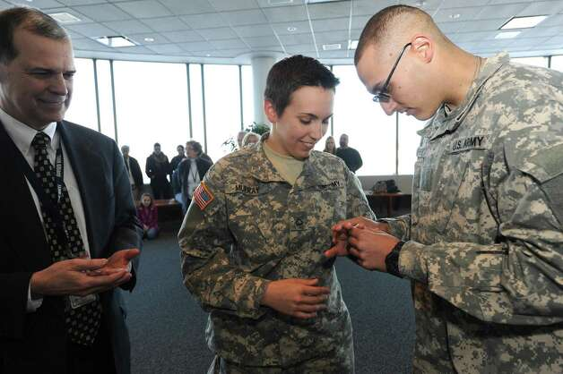 Army Privates, Caitlin Murray of Nassau and Sean Whitney of Niskayuna, are married by Town of Marriage Officer Lisa Armao Thursday Jan. 3, 2013, at  Albany International Airport in Colonie, N.Y. Airport Chief Executive Officer John A. O'Donnell, left, served as ring bearer and best man. (Michael P. Farrell/Times Union) Photo: Michael P. Farrell