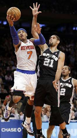 Carmelo Anthony takes it to the goal past Tim Duncan. Anthony had a game-high 23 points. Photo: Kathy Willens, Associated Press