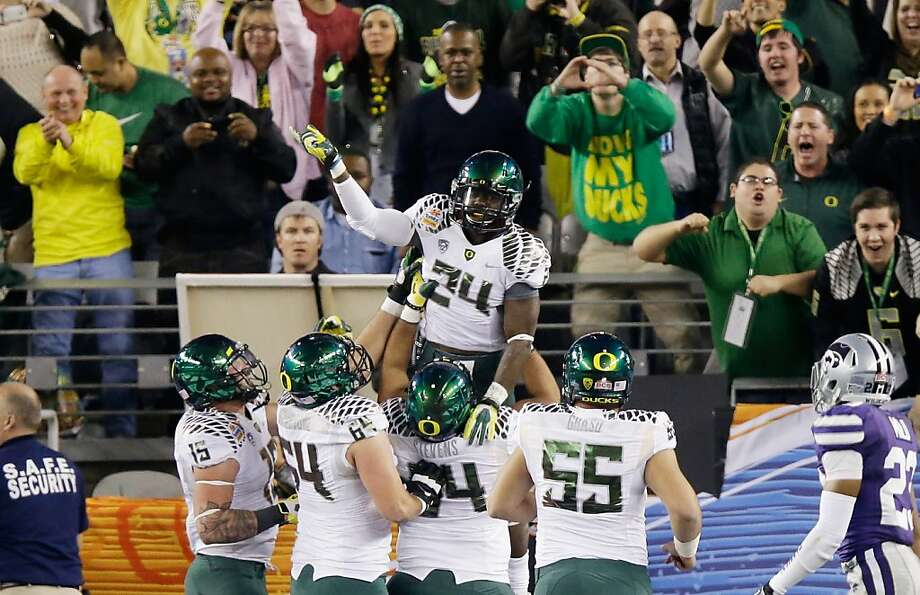 Oregon's Kenjon Barner gets a lift while celebrating after scoring on a pass from Marcus Mariota jus