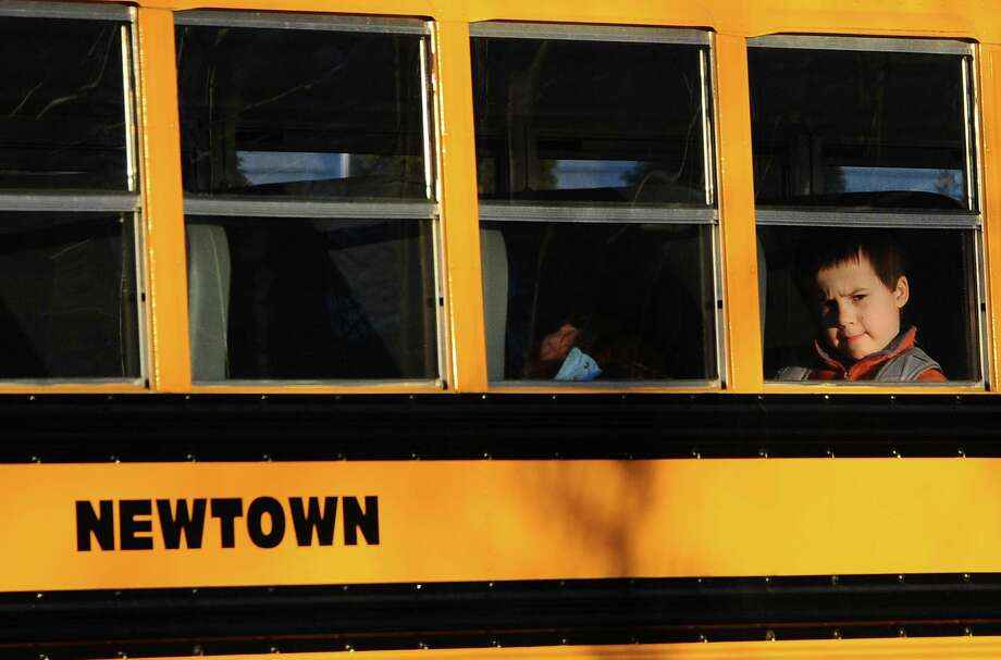 A boy sits on a Newtown bus leaving the new Sandy Hook Elementary School after the first day of classes in Monroe, Conn., Thursday, Jan. 3, 2013.  The Sandy Hook students started today in a new school, formerly called Chalk Hill School in Monroe.  It was renamed Sandy Hook Elementary and overhauled especially for the students from the Sandy Hook School shooting. (AP Photo/Jessica Hill) Photo: Jessica Hill