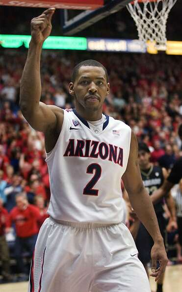 Arizona's Mark Lyons reacts after making a basket and foul shot during the second half of an NCAA co