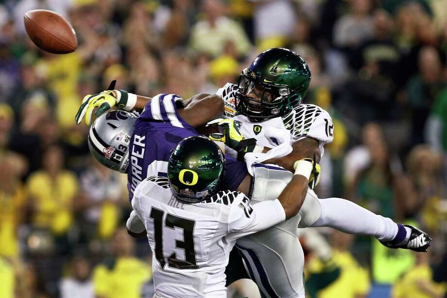 Oregon's Brian Jackson, right, and Troy Hill separate Kansas State's Chris Harper from the football during the Ducks' 35-17 win Thursday night. Photo: Ross Franklin, STF / AP