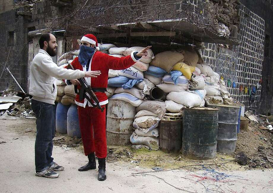 In this picture taken on Tuesday, Jan. 1, 2013, a citizen journalism image provided by Lens Young Homsi, which has been authenticated based on its contents and other AP reporting, a Free Syrian Army fighter wears as a Santa Claus suit and holds his AK-47, right, as he directs a civilian man, in the old city of Homs, Syria. Photo: Lens Young Homsi, Associated Press