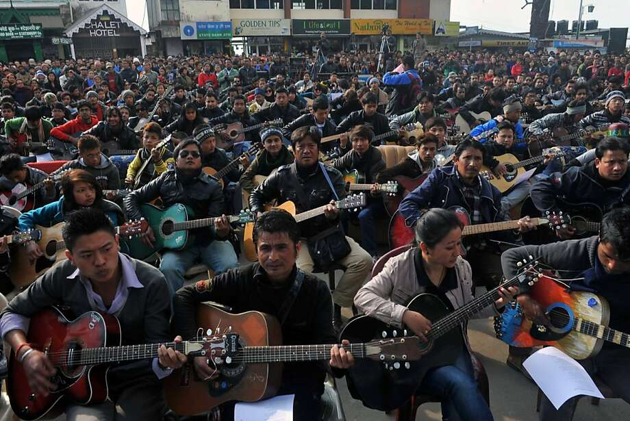 "Musicians play John Lennon's ""Imagine"" in a memorial tribute to the 23-year old Indian gang rape victim, during a mass guitar ensemble played by some 600 guitarists in Darjeeling on January 3, 2013. Protesters have massed in Indian cities daily since the December 16 assault demanding the government and police take sex crime more seriously, with tougher penalties for offenders and even chemical castration being considered. Five men accused of gang-raping a 23-year-old student on a moving bus in New Delhi in a deadly crime that repulsed the nation are to be formally charged in court January 3. Photo: Diptendu Dutta, AFP/Getty Images"