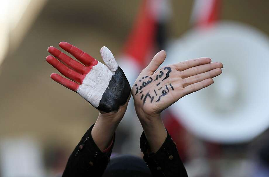 "A Yemeni pro-democratic female protestor shows her hands painted in the colours of her national flag and text reading in Arabic: "" We want the implementation of the decisions"" during a demonstration in Sanaa on January 3, 2013, demanding a quicker enforcement of President Abdrabuh Mansur Hadi's latest orders to restructure Yemen's military. Photo: Mohammed Huwais, AFP/Getty Images"
