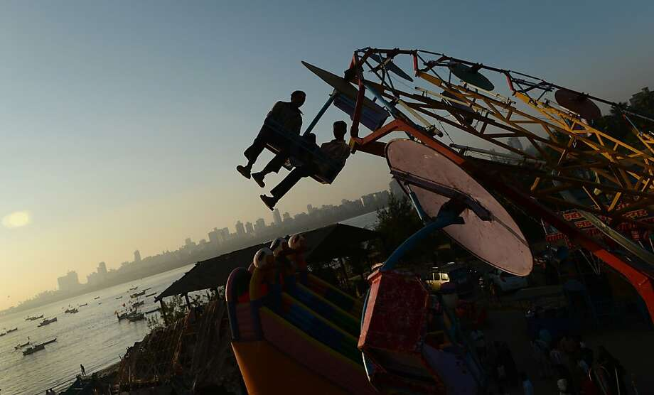Indian revellers enjoy an amusement park ride during an annual fair in Mumbai on January 3, 2013. The ten day-long fair is being held in honour of the Sufi saint Makhdoom Ali Mahimi on the dusty Mahim beach, which is full of people on giant wheels, toy trains and enjoying gravity-defying stunts in the 'Maut Ka Kuan' or 'Valley of Death'. Photo: Punit Paranjpe, AFP/Getty Images