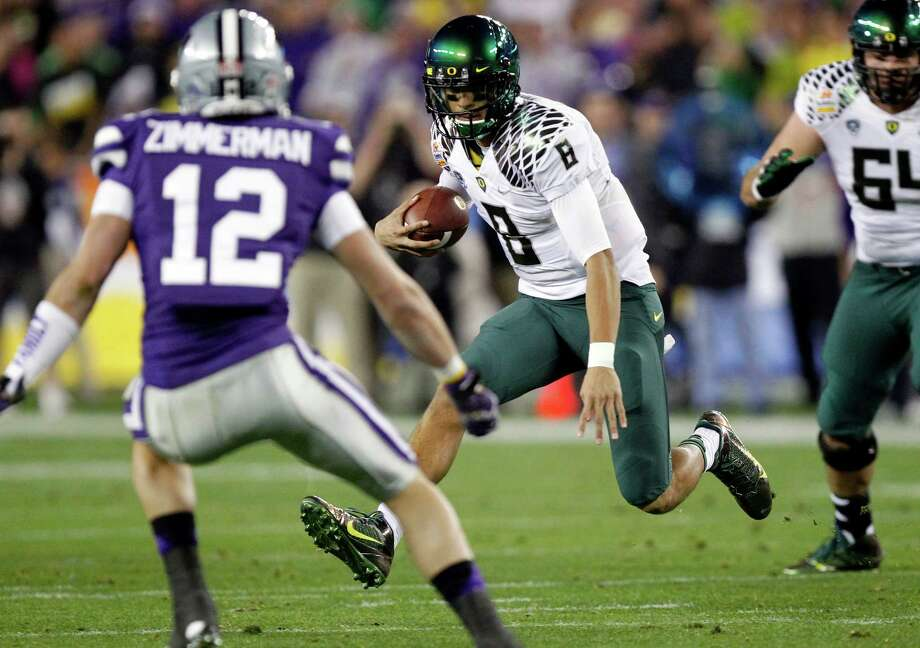 Oregon quarterback Marcus Mariota (8) tries to avoid Kansas State defensive back Ty Zimmerman (12) during the first half of the Fiesta Bowl NCAA college football game, Thursday, Jan. 3, 2013, in Glendale, Ariz. (AP Photo/Paul Connors) Photo: Matt York