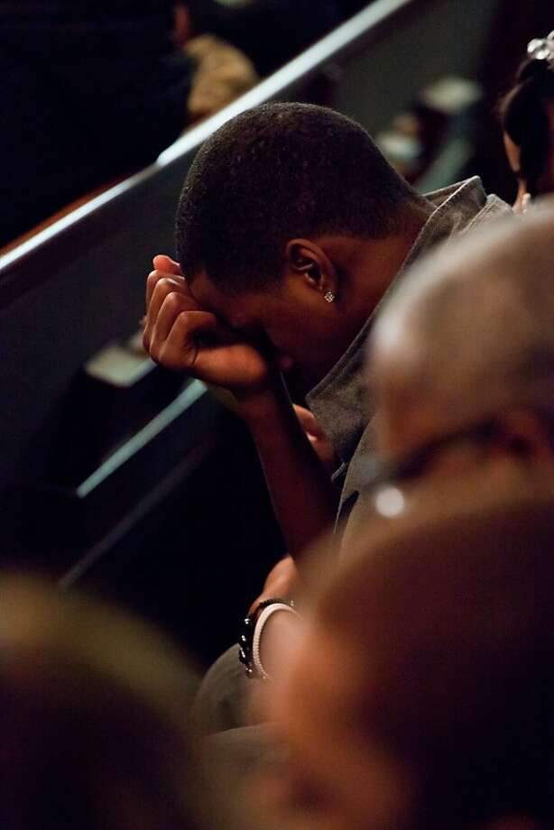 A mourner bows his head in prayer during the funeral for LeTroy Edwards, 43, his wife Selena Carranza, 37, and her son Jayson Cobbin, 11, who all died Christmas morning due to carbon monoxide poisoning, on Thursday, Jan. 3, 2012, at Antioch Missionary Baptist Church in Flint, Mich. Photo: Griffin Moores, Associated Press