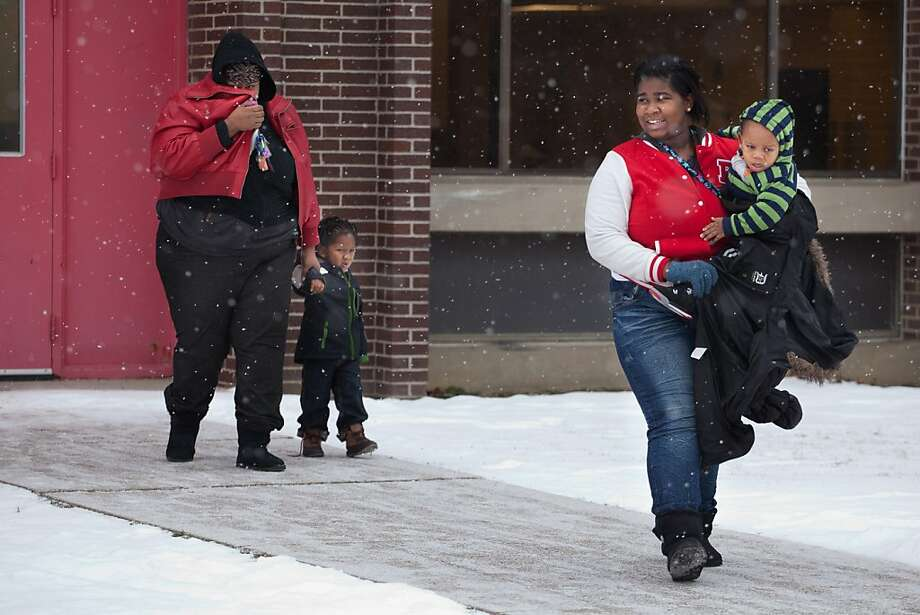 Nicoy Williams, 14, right, who is in 9th grade at Flint Northern High School, walks out of the building carrying one of her younger siblings after being picked up by her mom following a report of a man with a gun at the school on Thursday, Jan. 3, 2012 in Flint, Mich. Flint school district spokesman Bob Campbell says the lockdown order at Northern High School was lifted around 9:55 a.m. Thursday after police searched the building. No weapons were found. Campbell says some parents picked up their children once the lockdown was lifted, but school was continuing for the day. Photo: Griffin Moores | MLive.com, Associated Press