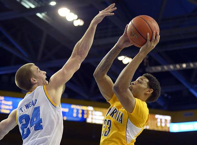 Allen Crabbe tries to maneuver around UCLA's Travis Wear. Crabbe had 21 points. Photo: Mark J. Terrill, Associated Press