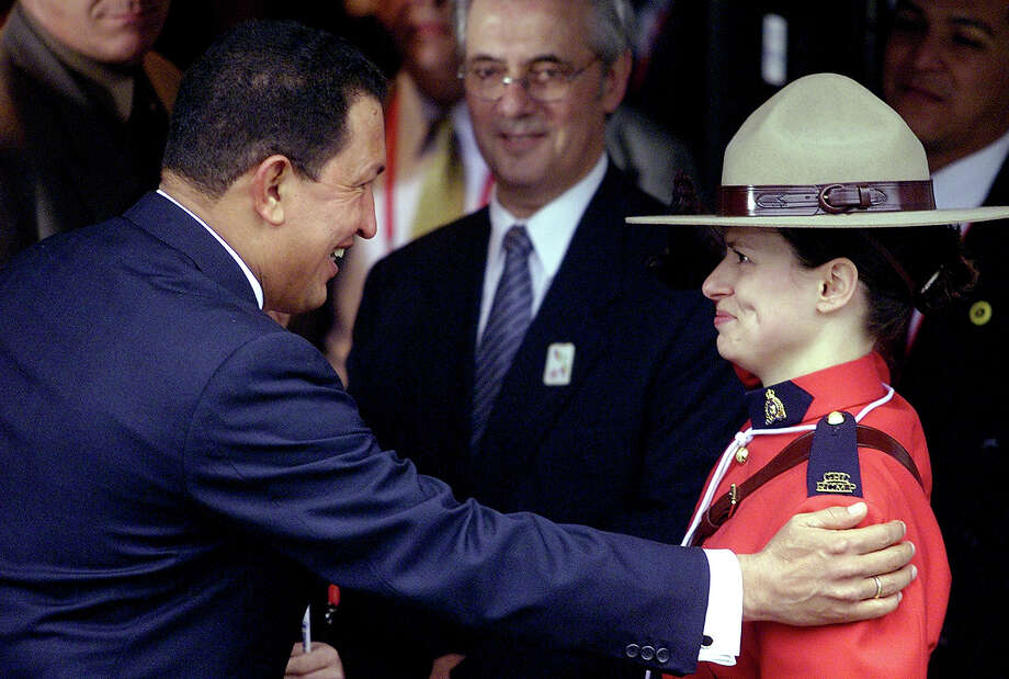 Venezuelan President Hugo Chavez greets Michelle Karpen a Canadian Mounted Police officer at the entrance of a local hotel in Quebec City in 2001. Photo: ANTONIO SCORZA, AFP/Getty Images / AFP