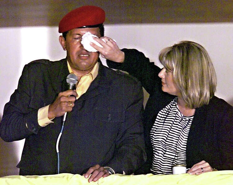 Venezuelan President Hugo Chavez speaks as his wife Marisabel de Chavez wipes sweat from his face as