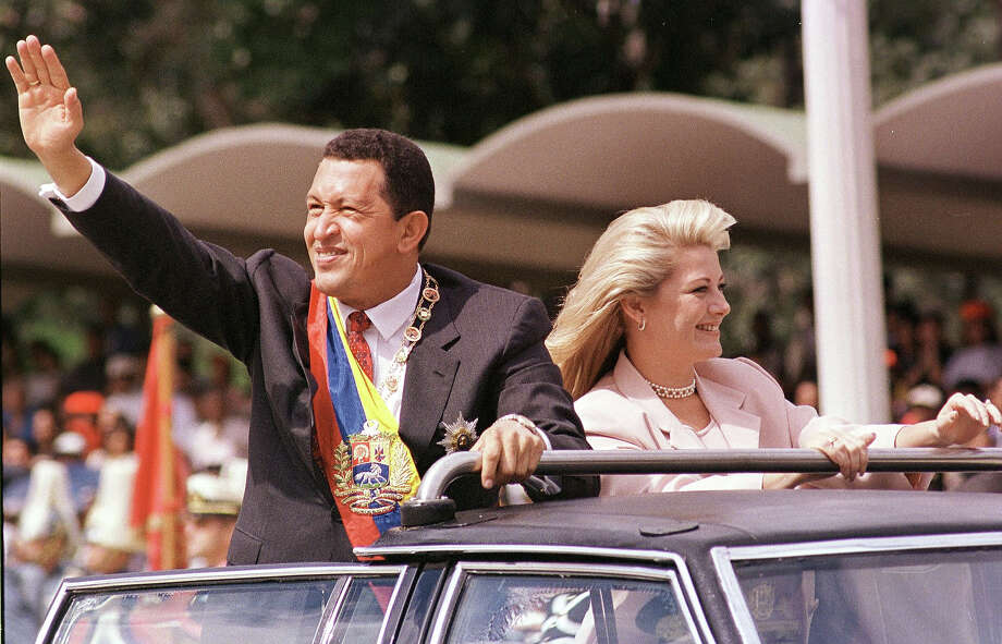 Venezuelan President Hugo Chavez, accompanied by his wife Marisabel Rodriguez de Chavez, waves to supporters. Photo: BERTRAND PARRES, AFP/Getty Images / AFP