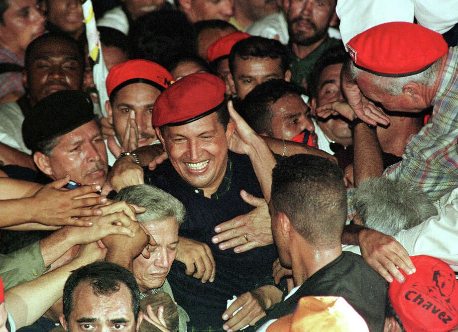 Venezuelan Presidential candidate Hugo Chavez is greeted by supporters as he arrives at his campaign closing rally in 2006. Photo: BERTRAND PARRES, AFP/Getty Images / 2012 AFP