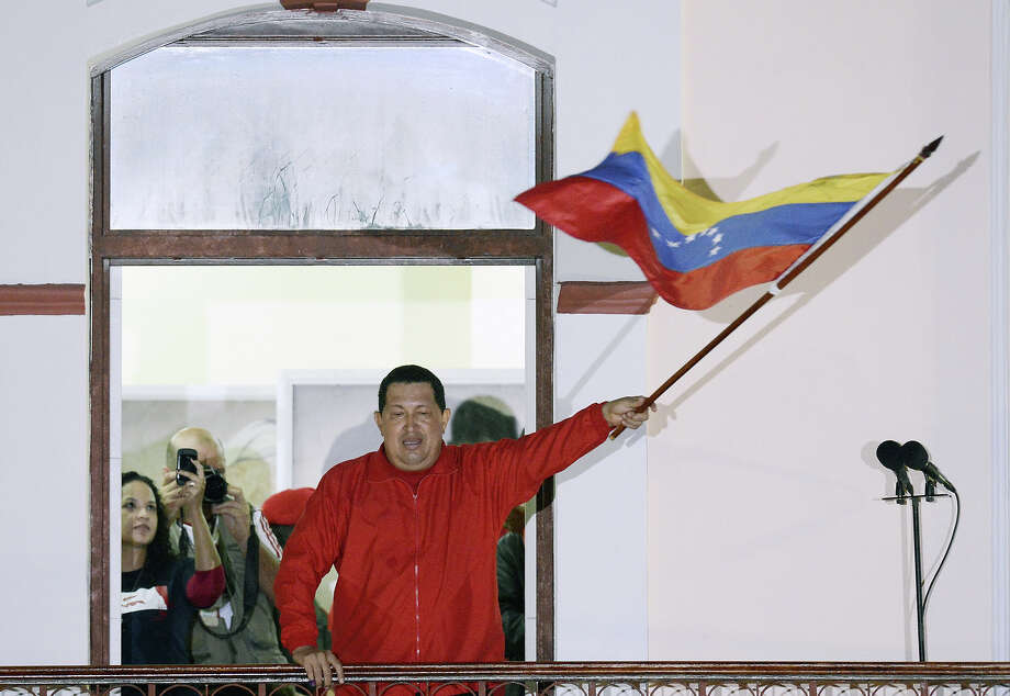Venezuelan President Hugo Chavez waves a Venezuelan flag while speaking to supporters after receiving news of his reelection in Caracas on October 7, 2012. According to the National Electoral Council, Chavez was reelected with 54.42% of the votes, beating opposition candidate Henrique Capriles, who obtained 44.97%. AFP PHOTO/JUAN BARRETO        (Photo credit should read JUAN BARRETO/AFP/GettyImages) Photo: JUAN BARRETO, AFP/Getty Images / 2012 AFP