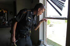 Harris County Sheriff Department Deputy Sean Simpson points out fingerprint evidence on a window at a home burglary Thursday, Aug. 9, 2012, in Houston.
