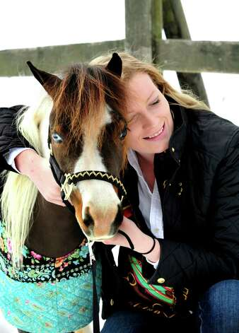 Therapy volunteer Chesleigh Slayton hugs Wakanda, one of the Gentle Carousel Miniature Therapy Horses visiting The Ridge Equestrian Center in Newtown Friday, Jan. 4, 2012. Photo: Michael Duffy / The News-Times