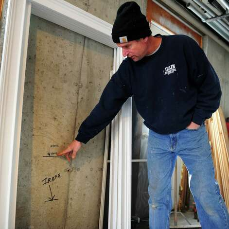 Bill Saley points to the lines on his basement wall where he recorded flood levels for Hurricanes Irene and Sandy Friday, Jan. 4, 2013 at his Marsh Street home in Milford, Conn.  Saley suffered only minor damage during Hurricane Sandy but acknowledges it was far worse for many of his neighbors. Photo: Autumn Driscoll / Connecticut Post