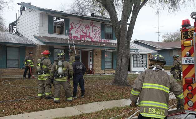 San Antonio firefighters battle a fire Friday January 4, 2013 at a two story house at 9614 Berryville on San Antonio's far West Side. According to San Antonio fire captain Ruben Cruz, the vacant home started burning about 8:50 a.m. in an upper story back room and burned through the home's floor. Cruz said arson is investigating the cause of the fire which caused about $50,000 in damages. There were no injuries during the incident. Photo: JOHN DAVENPORT, San Antonio Express-News / ©San Antonio Express-News/Photo Can Be Sold to the Public