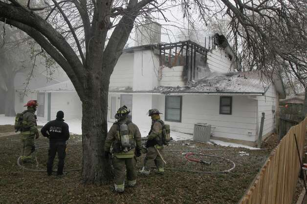 San Antonio firefighters stand behind a house after fighting a fire Friday January 4, 2013 at a two story house at 9614 Berryville on San Antonio's far West Side. According to San Antonio fire captain Ruben Cruz, the vacant home started burning about 8:50 a.m. in an upper story back room and burned through the home's floor. Cruz said arson is investigating the cause of the fire which caused about $50,000 in damages. There were no injuries during the incident. Photo: JOHN DAVENPORT, San Antonio Express-News / ©San Antonio Express-News/Photo Can Be Sold to the Public