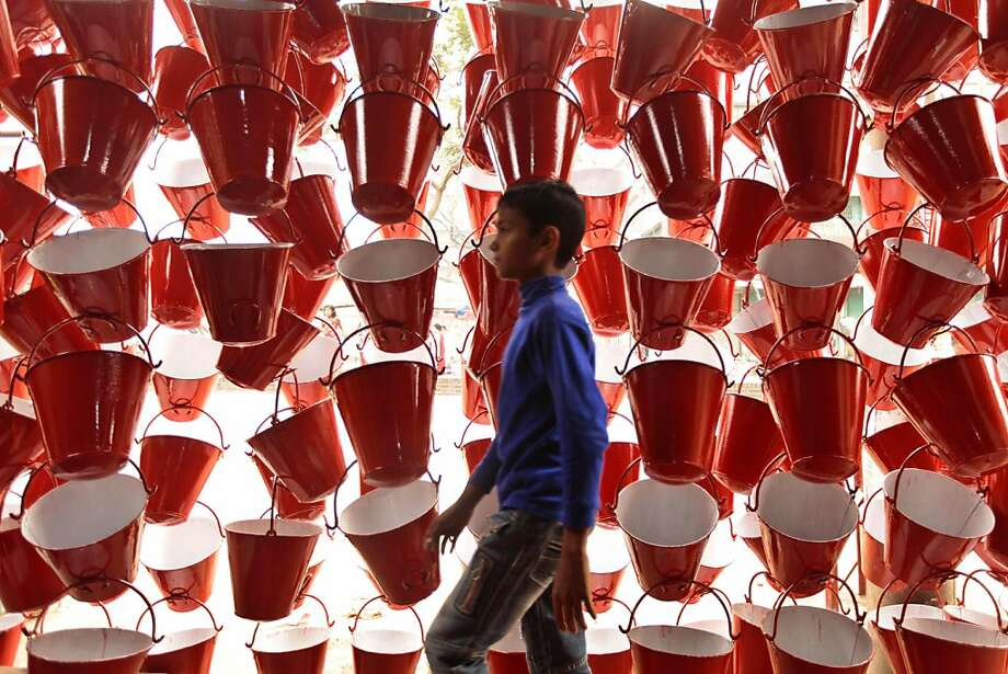 Buckets R Us: A young Bangladeshi boy walks past a specialty shop in Dhaka. The pails are kept by garment factories in case of fires. Photo: A.M. Ahad, Associated Press