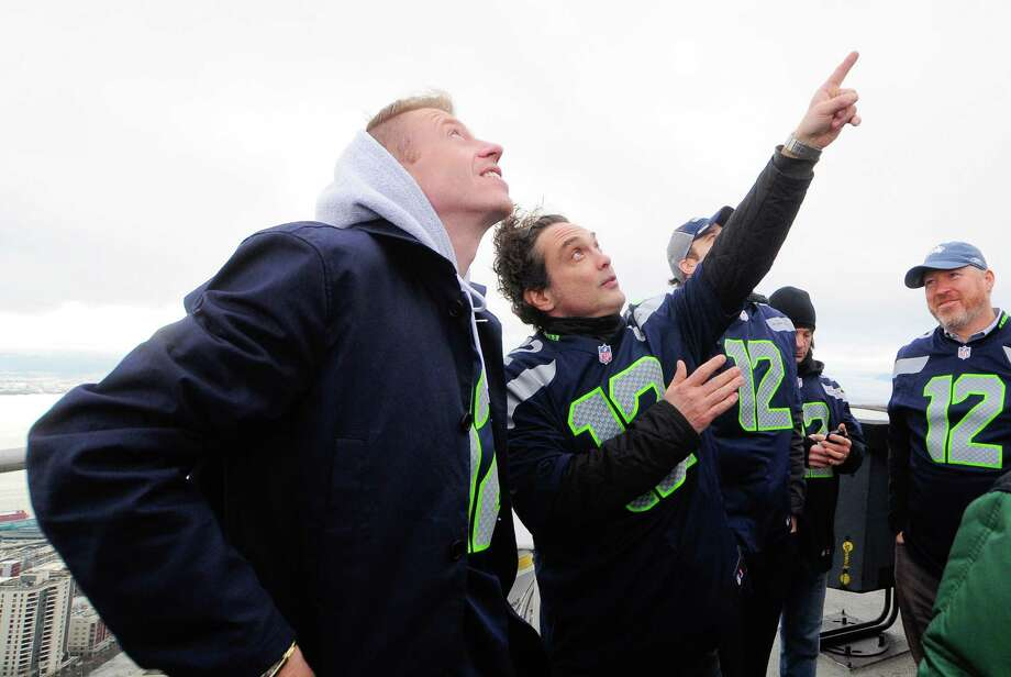Macklemore looks on as Jason Finn of Presidents of the United States of America points to the flag pole on the Space Needle roof on Friday.  Photo: LINDSEY WASSON, Seattlepi.com / SEATTLEPI.COM
